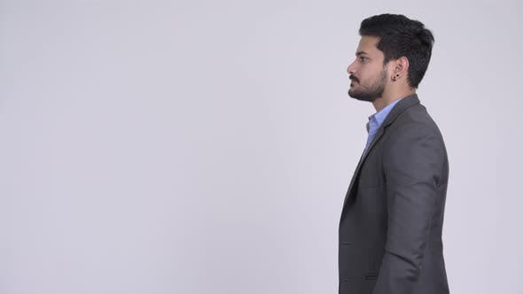 Thumbnail for Profile View of Young Handsome Bearded Indian Businessman Wearing Suit