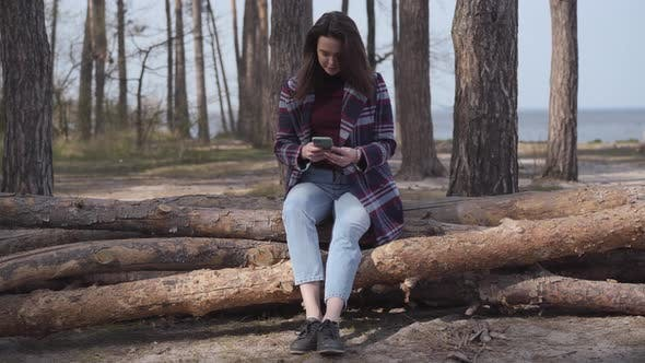 Thumbnail for Happy Smiling Woman Sitting on Log in Forest and Using Smartphone. Brunette Caucasian Girl Resting