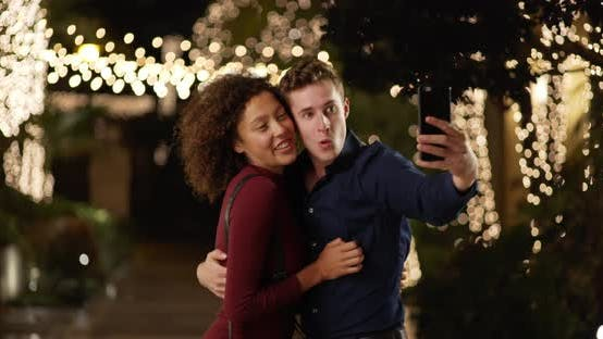 Cover Image for Cheerful couple take selfie with smartphone, smiling and laughing