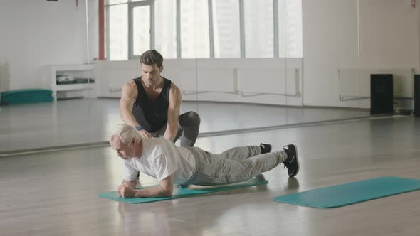Thumbnail for Fitness Coach Helping Senior Man Training Plank Exercises in Sport Club
