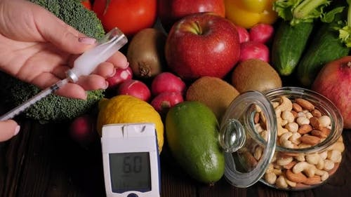 A Diabetic Dialling Insulin Into a Syringe on the Background of a Fresh Fruits