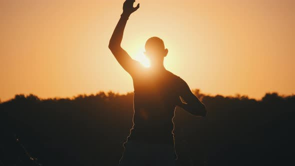 Thumbnail for Silhouette of Man Against Sunset Raising Hands Up. Freedom. Slow Motion