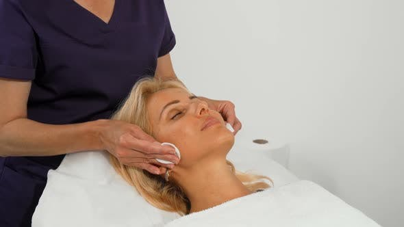 Mature Woman Getting Facial Cleanse Treatment By Cosmetologist