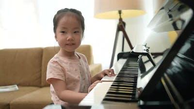 Medium Close up shot asian toddler practicing piano.