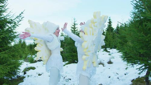 Women jumping in snowflakes costumes