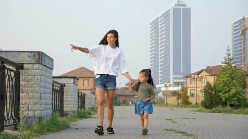 Mother Walks with Korean Little Girl Along Embankment
