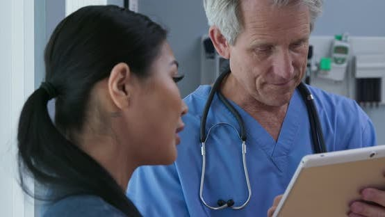 Thumbnail for Doctor showing tablet computer with results to patient in hospital exam room
