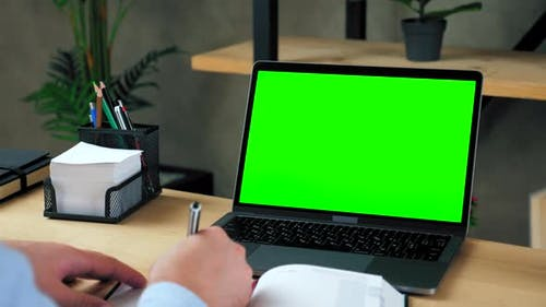 Man student study writes information in notebook. Green screen laptop computer