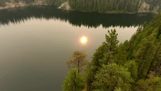Flying Around Island with Smoke-Obstructed Sun Reflected on River