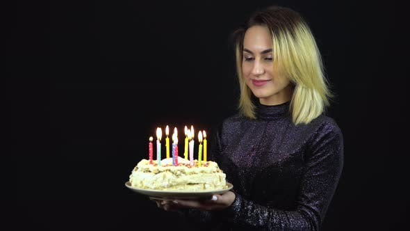 Thumbnail for The Girl Holds a Holiday Cake with Candles. A Young Woman Is Standing in a Shiny Evening Dress