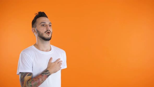 Young Man in Soccer Football Uniform Singing a Hymn Isolated at Orange Background