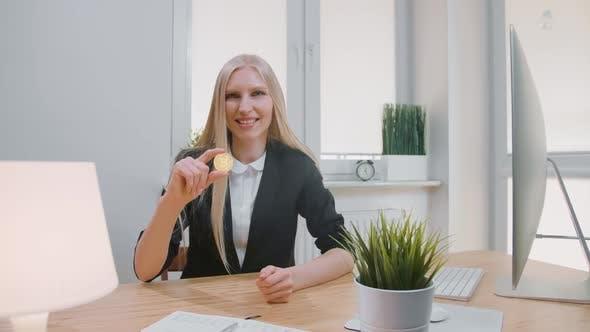 Thumbnail for Glückliche Frau mit Bitcoin zeigt Daumen nach oben. Lächelnde fröhliche Blonde Frau im Büro Anzug sitzt bei