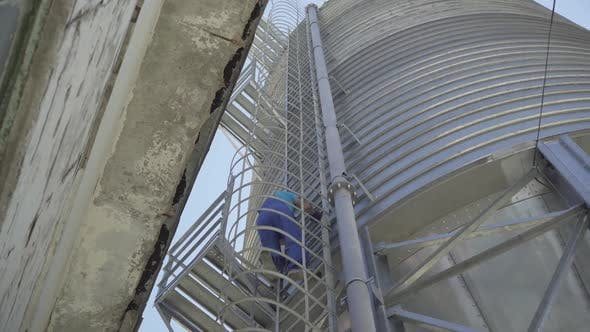 Thumbnail for Wide Shot of Man in Uniform and Safety Helmet Walking on Enormous Cement Storage Silo. Huge