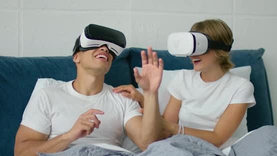 Thumbnail for Young Mixed Couple Lying in Bed, Watching 360 Video in Virtual Reality Headsets