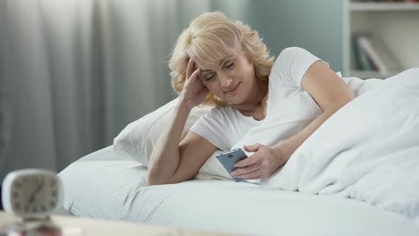 Thumbnail for Smiling Mature Woman Lying in Bed and Checking E-Mail on Smartphone, Morning