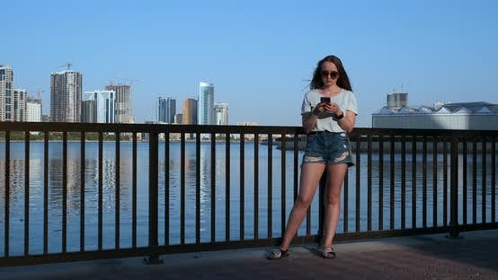 Thumbnail for Beautiful Girl with Long Hair in Sunglasses Using Smartphone App at Sunset River Quay Near