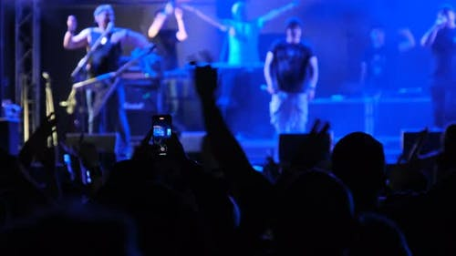 Crowd of People at a Rock Concert Raises His Hands Up and Applauds Fans