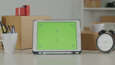 Tablet with blank green screen template on the table.