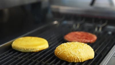 Cooking burgers at restaurant. Close up of chief cooking tasty burger at restaurant