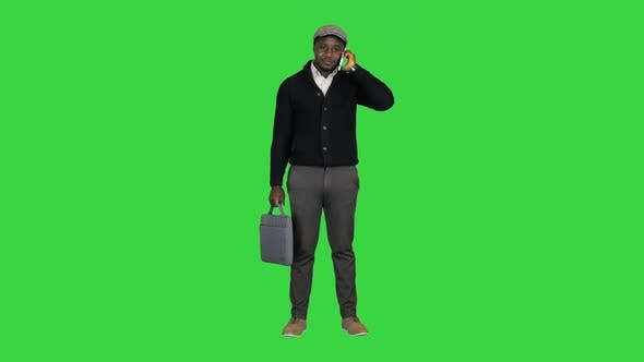 Happy African American Man in a Hat Talking on the Phone on a Green Screen Chroma Key