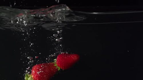 Three Juice Strawberryes Splashing Into Water in Slowmotion