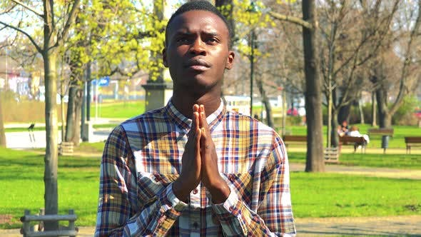 Thumbnail for A Young Black Man Prays with Hands Clasped Together in a Park on a Sunny Day