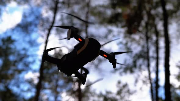 Thumbnail for Drone with a Camera Hovers in the Air. Flies Above the Ground in the Forest. Slow Motion