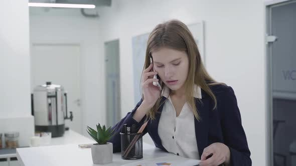 Cover Image for Concerned Young Lady in Formal Dress Talking By Cellphone Checking Papers in the Office Standing at
