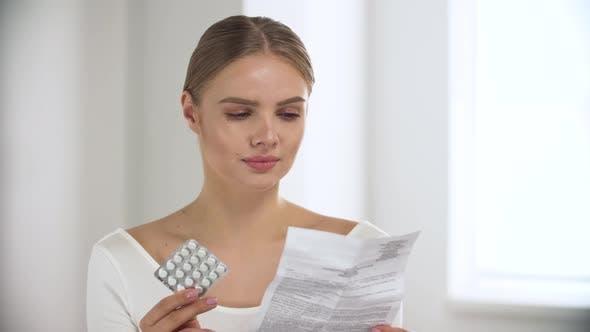 Medicament. Woman Reading Pills Instruction At Light Interior