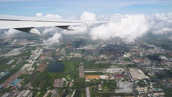 Thumbnail for The airplane flies through the clouds above the earth, city roads and rooftops are visible below