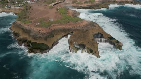 Thumbnail for Aerial drone view of ocean waves and swell crashing into a rocky coastline