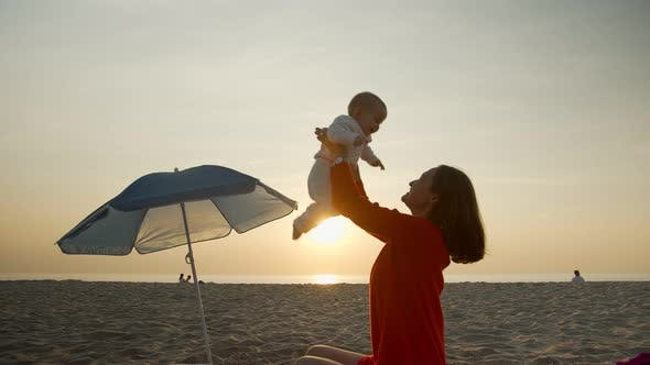 Glückliche Mutter mit Baby auf Sonnenuntergang Hintergrund