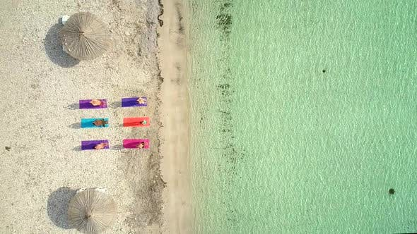 Aerial view of yoga group on mats on beach with parasols.