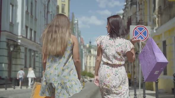 Cover Image for Two Cheerful Women with Shopping Bags Walking Through City Street