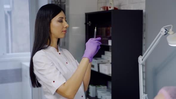 Thumbnail for Niedlicher Kosmetiker mit langem Haar überprüft eine Spritze vor dem Botox-Verfahren