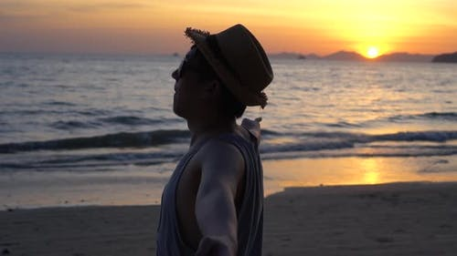 Silhouette Back of Young Male Travel Backpacker Doing Peace v Sign Finger Against Sunset