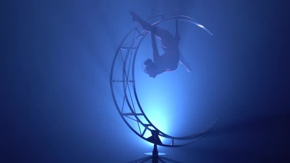 Thumbnail for Gymnast in a Brilliant Costume Performs Tricks on a Special Design Moon. Blue Smoke Background