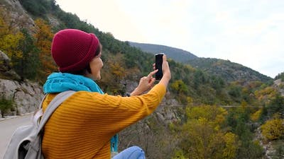 Woman with Backpack Using Smartphone Hiking In The Mountains