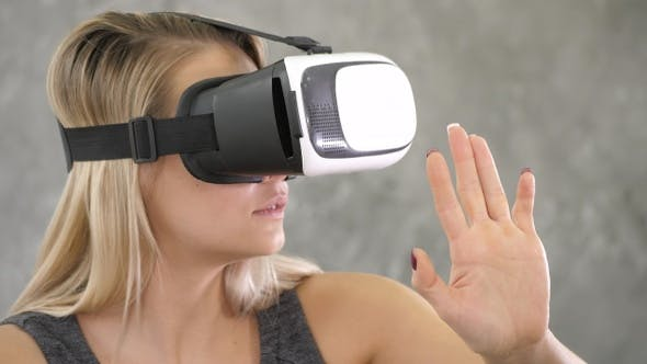 Thumbnail for Young woman wearing virtual reality device over grey background.