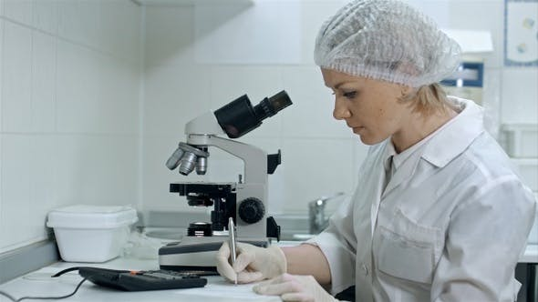 Thumbnail for Scientist Working with Microscope Calculating and Taking