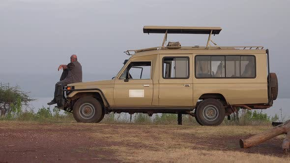 A Male Tourist Watches Africa Landscape by Safari Vehicle