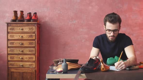 Cheerful Guy Drawing Something at Shoe Repair Shop.