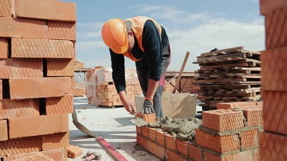 Close Up of a Man Building a Brick House