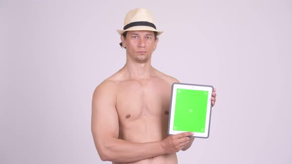 Thumbnail for Happy Muscular Tourist Man Smiling While Showing Digital Tablet Shirtless