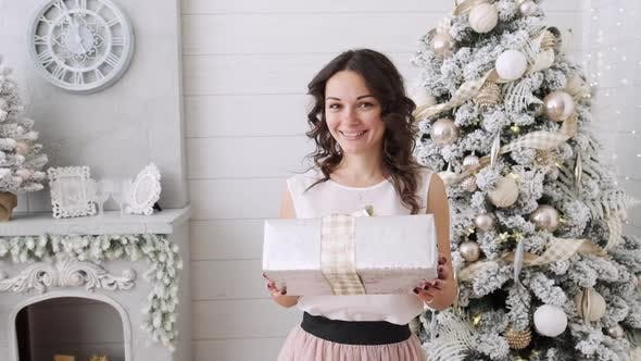 Attractive Brunette with Christmas Gifts on a Background of a Beautiful Interior. Christmas House