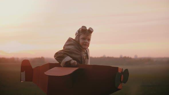 Thumbnail for Happy Little Pilot Boy Starts To Run in Fun Cardboard Plane on Sunset Autumn Field, Playing