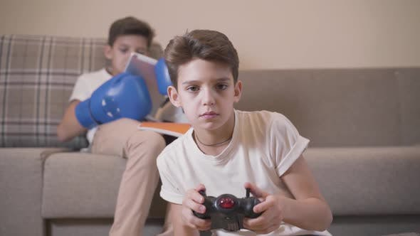Thumbnail for Close-up Portrait of Cute Caucasian Boy Playing Game Console As His Twin Brother Reads