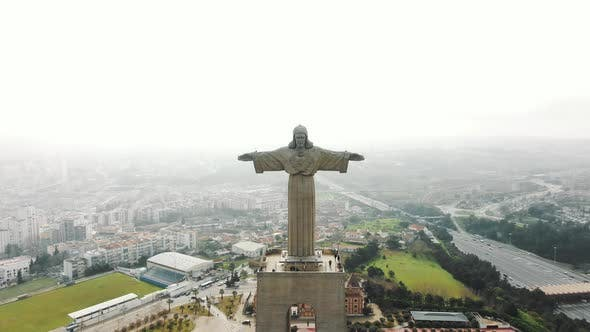 Majestic Jesus Monument Against White Cloudy Sky and Lisbon