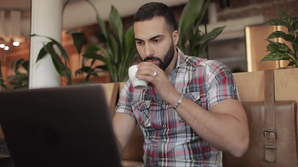 Man Drinking Coffee and Working on Laptop