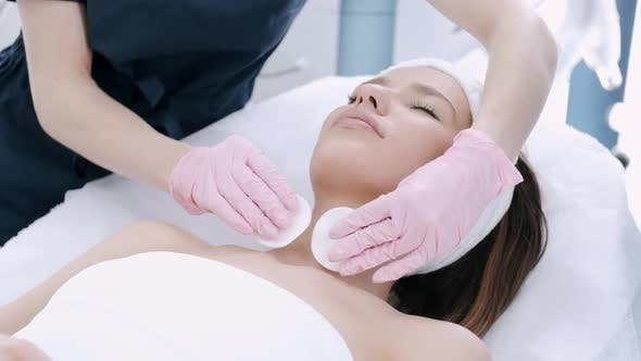 Cropped View of Cosmetologist Cleansing Woman's Skin with Pads